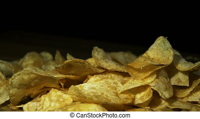 Potato Chips Rotating On Black Background. Potato chips are...