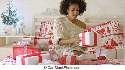 Young woman sitting in bed surrounded by gifts
