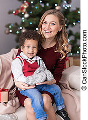 Happy charming woman having her son on the lap