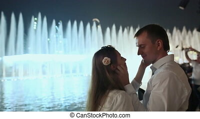 Love couple enjoying each other on the background of night city fountains