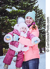 happy family mother and baby girl daughter in winter outdoors