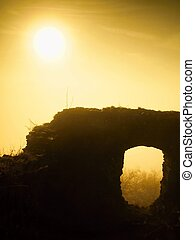 The stronghold. Stony ruin of medieval stronghold tower on hill. Early morning sunshine hidden in heavy autumn mist.