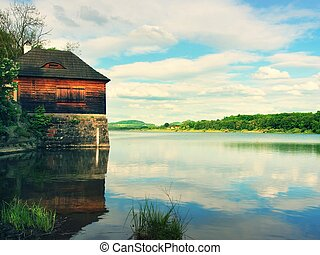 Morning lake with old style wooden fishing hut on the right bank, reflection of sky