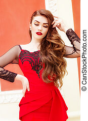 Beautiful young girl in a red evening long dress. The beauty...