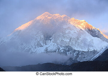 sunset on snow capped mountain on the way to everest base...