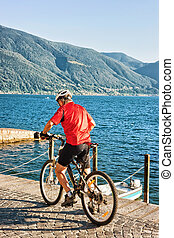 Man riding bicycle at promenade in Ascona of Ticino...