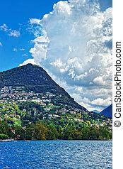 Swiss houses at Lake Lugano and Alps mountains Ticino...