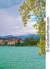 Houses at Lake Lugano and mountains in Ticino Switzerland -...