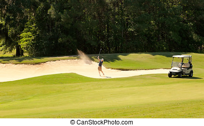 Young golfer in Sand Bunker - Young male golfer hitting out...