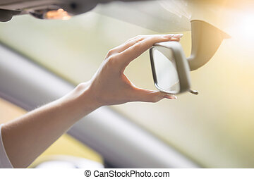 Young woman adjusting a rear-view mirror in the car - Young...
