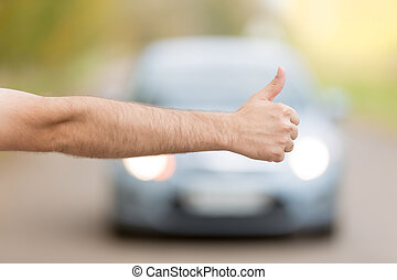 Close up of male hand hitchhiking, asking a coming car for a...