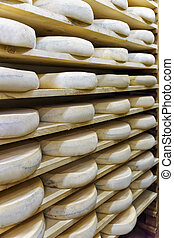Wheels of aging Cheese at maturing cellar Franche Comte...
