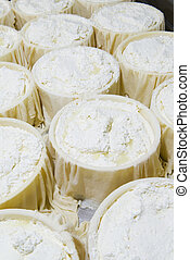 Pieces of fresh cheese wrapped in cloth canvas during the...