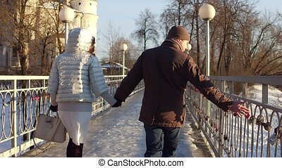 Man and woman walking holding hands on a small bridge full of love locks.