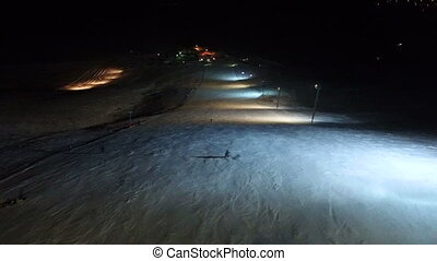 Skier making tricks on the night slope. - Night skiing and...