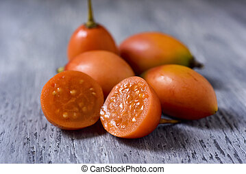 tamarillo fruits on a wooden table - closeup of some...