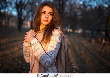 Sunset portrait of beautiful brunette young woman in autumn park