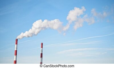 Chimneys of Power Plant on blue sky. White vapor from red tube,