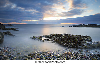 Early morning landscape of ocean over rocky shore with glowing sunrise