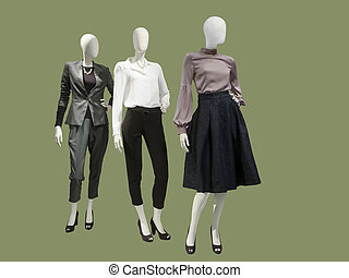 Three female mannequins dressed with fashionable clothes.