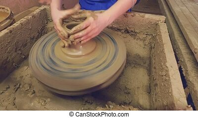Potters wheel. Womens hands are trying to make Pot -...