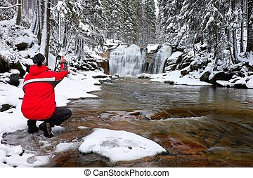 Photograph in red jacket with digital camera in hands is...