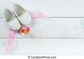 Expecting a baby background with shoes and a pacifier on a...