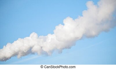 Smoke stack with a thick smoke plume over blue sky,...