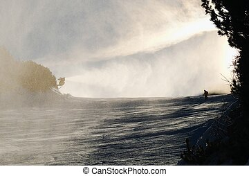 Snowmaking on slope. Skier near a snow cannon making fresch...