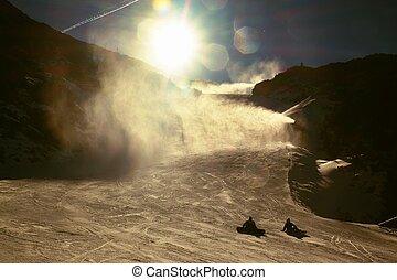 Skier in slope. A snowgun makes fresh powder snow. Snow...