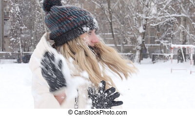 winter woman play snowballs - girl playing snowballs in the...