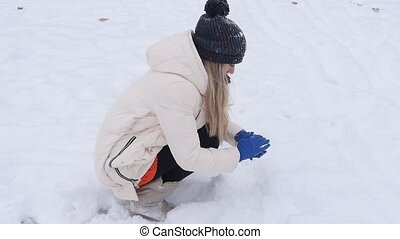 girl makes snowballs - Young woman holding natural soft...