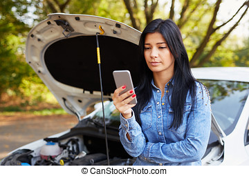 Young woman standing in front of a broken car with mobile...