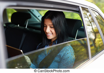 Happy woman sitting in a car with tablet
