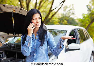 Young woman with a broken car calling for assistance