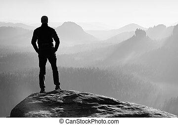 Hiker is standing on peak of sandstone rock in rock empires...