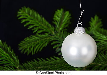 Silver white bauble Christmas ornament over fir branch -...