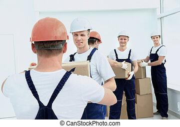 stevedores unload boxes in new premises - workers unload...