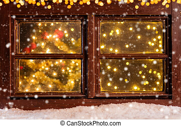 Atmospheric Christmas window with falling snow and blur...