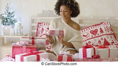 Young woman sitting in bed surrounded by gifts - Young woman...