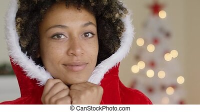 Sensual young woman in a Santa Claus outfit cuddling down...