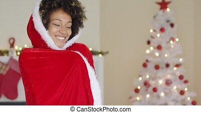 Attractive woman in a red Santa cape with hood standing in...