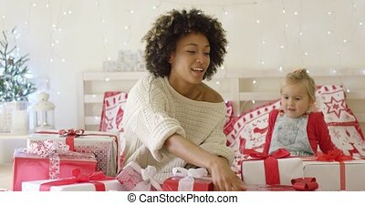 Mother showing female child Christmas gifts