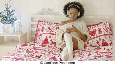Beautiful woman in long sweater on bed