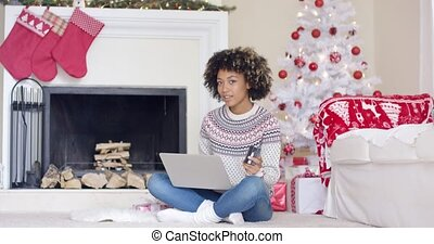 Young woman doing Christmas shopping online sitting on the...
