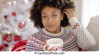Smiling friendly young woman relaxing at Christmas in front...