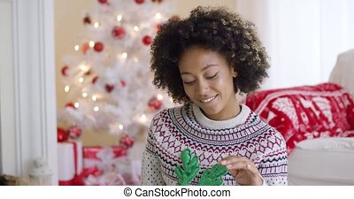 Cute young woman with toy green antlers while sitting in...