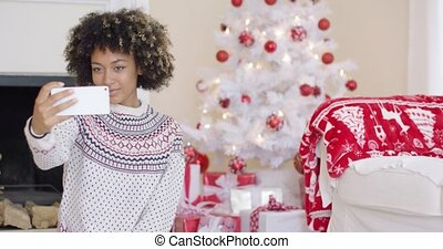 Happy young woman posing for a Christmas selfie on her...