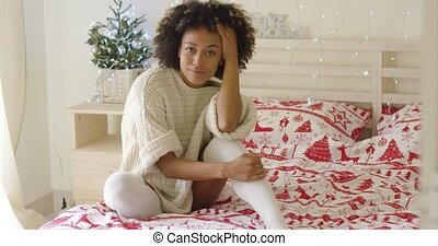 Beautiful young woman sitting in bed with Christmas theme...