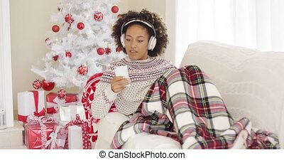 Happy woman listening to music on Christmas Day